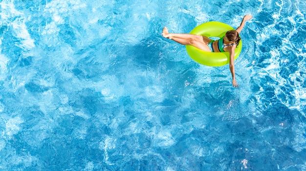 Jovem ativa na piscina aérea vista superior de cima, criança relaxa e nada no anel inflável donut e se diverte na água em férias em família, resort de férias tropical