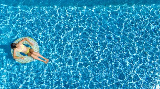 Jovem ativa na piscina aérea vista superior de cima,