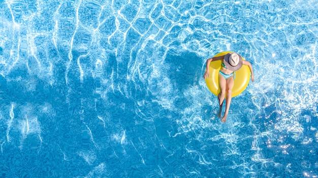 Jovem ativa na piscina, vista aérea de cima, criança relaxando e nadando em um anel de rosca inflável e se divertindo na água em um resort de férias tropicais de férias com a família