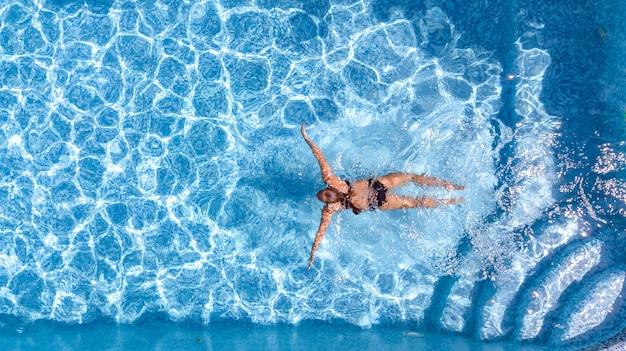 Jovem ativa na piscina vista aérea do drone de cima. jovem nadando na água azul