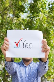 Jovem, ativista liga para votar segurando papel com declaração sim. ativismo político, processo eleitoral, conceito de posições de vida ativa. presidente, eleições constitucionais.