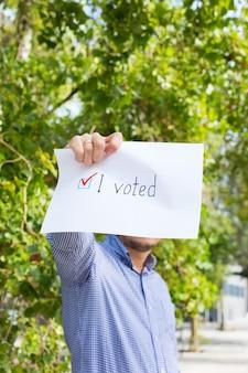Jovem, ativista liga para votar segurando um papel com a declaração eu votei. ativismo político, processo eleitoral, conceito de posições de vida ativa. presidente, eleições constitucionais.