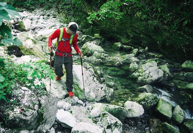 Jovem ativo caminhando com bastões de trekking nas pedras ao longo do rio da montanha