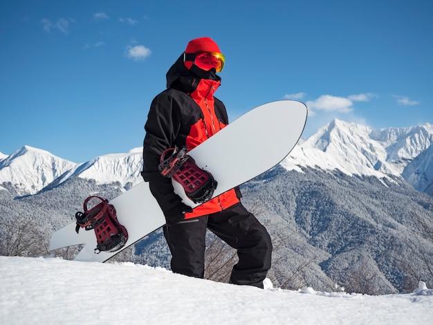 Jovem ativo com pé de snowboard cauda de andorinha branca na neve no fundo de montanhas. estação de esqui rosa khutor