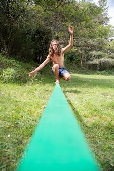 Jovem ativo com torso nu balanceamento no slackline em campo verde no verão