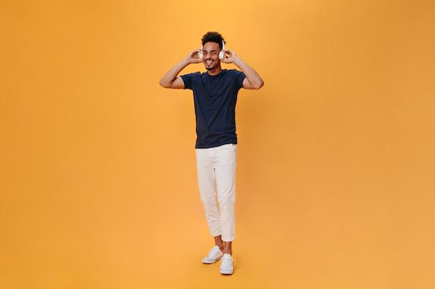 Jovem ativo em calças leves coloca fones de ouvido