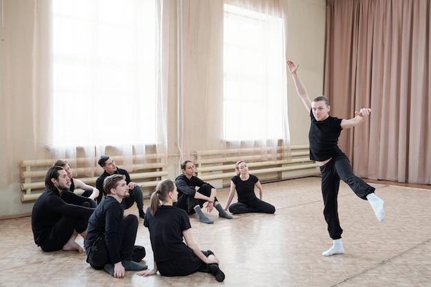 Jovem ativo em pé no chão enquanto mostra um dos exercícios de dança para um grupo de alunos durante o treinamento em estúdio