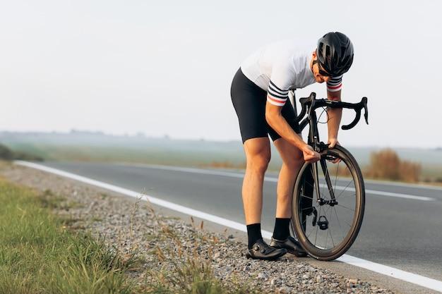 Jovem ativo em roupas esportivas em pé entre os campos e consertando uma bicicleta preta em uma estrada pavimentada