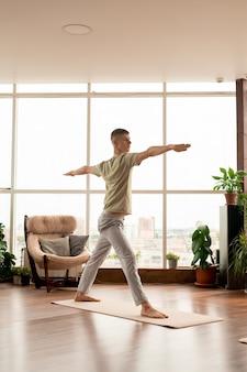 Jovem ativo em roupas esportivas, em pé no tapete com os braços estendidos durante o treinamento de ioga em casa