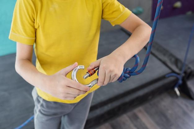 Jovem ativo segurando o mosquetão com corda enquanto prepara o equipamento para escalada antes do treino na academia de lazer