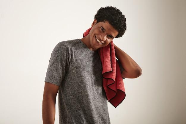 Jovem atleta afro-americano de cabelos encaracolados escuros, sorridente, vestindo uma camiseta técnica cinza, limpando o pescoço com uma toalha de microfibra waffle vermelha no branco