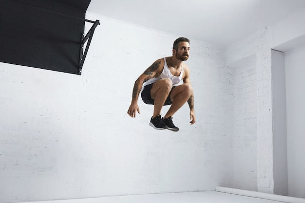 Jovem atleta barbudo e tatuado mostra movimentos calistênicos, pula alto ao lado de pullbar preto, vestindo camiseta sem manga, isolado na sala branca do centro de fitness