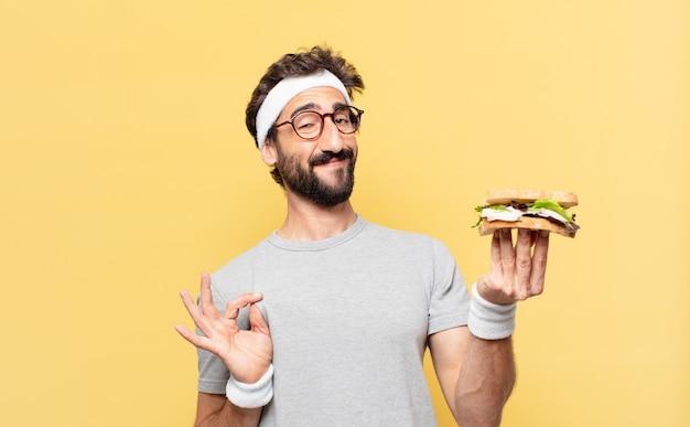 Jovem atleta barbudo maluco com expressão feliz e segurando um sanduíche