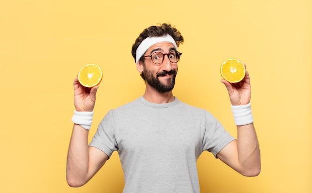 Jovem atleta barbudo maluco com expressão feliz e uma laranja
