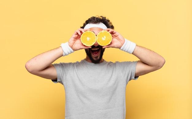 Jovem atleta barbudo maluco com expressão surpresa e uma laranja