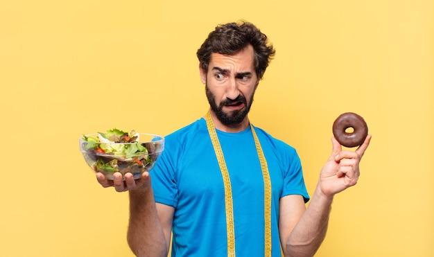 Jovem atleta barbudo maluco duvidando ou expressão incerta, segurando rosquinha de chocolate e salada