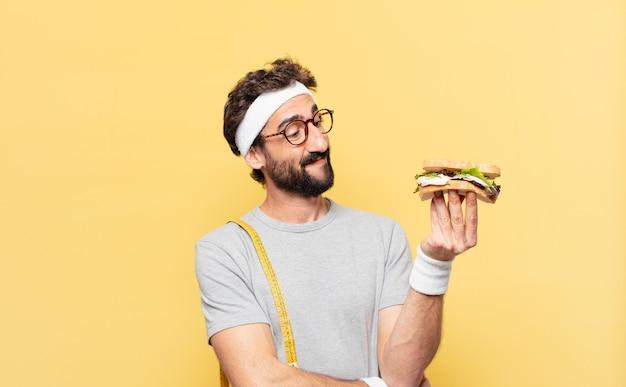 Jovem atleta barbudo maluco pensando em expressão e segurando um sanduíche