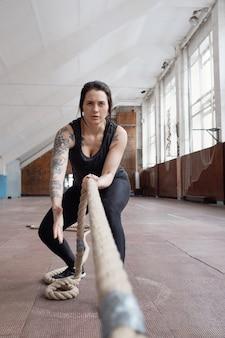 Jovem atleta caucasiana atraente com tatuagens puxando cordas de batalha enquanto faz exercícios de treinamento cruzado no ginásio