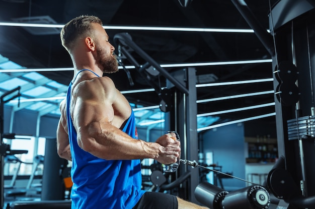 Jovem atleta caucasiano musculoso treinando na academia, fazendo exercícios de força, praticando, trabalhando na parte superior do corpo, puxando pesos e halteres. fitness, wellness, conceito de estilo de vida saudável, trabalhando.