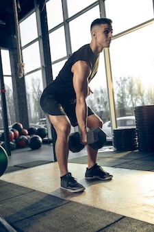 Jovem atleta caucasiano musculoso treinando na academia, fazendo exercícios de força, praticando, trabalhando na parte superior e inferior do corpo, abdominais com pesos. fitness, wellness, conceito de estilo de vida saudável.