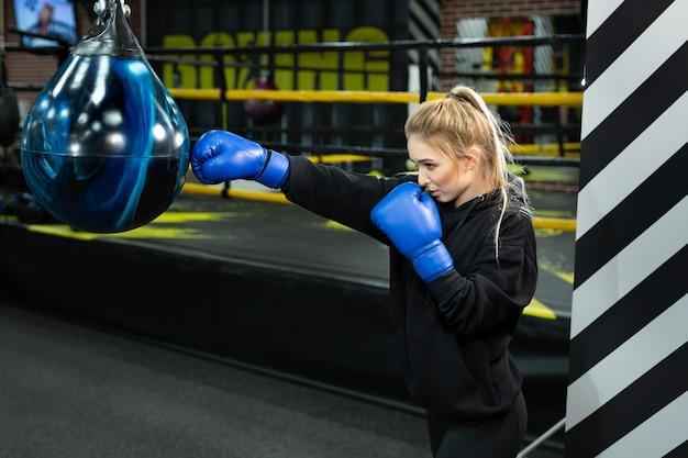 Jovem atleta com luvas de boxe azuis atinge uma pêra no ringue