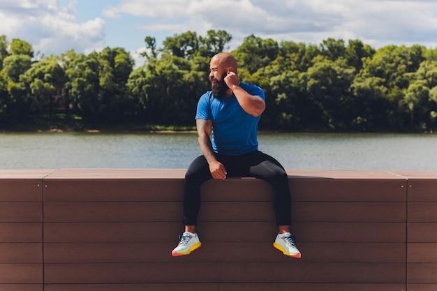 Jovem atleta correndo rápido ao ar livre. vestindo roupa esportiva, dando passos largos, demonstrando um modo de vida saudável, tiro amplo.