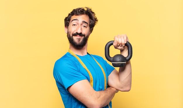 Jovem atleta de barba maluca jovem atleta de barba maluca expressão feliz e levantando halteres