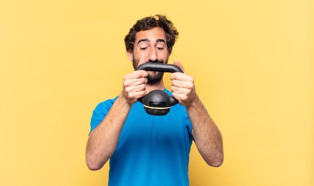 Jovem atleta de barba maluco jovem atleta de barba maluco expressão feliz e levantando halteres