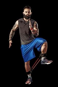 Jovem atleta de cócoras exercício com banda de resistência ao redor das pernas. comprimento de corpo inteiro sobre fundo preto studio.