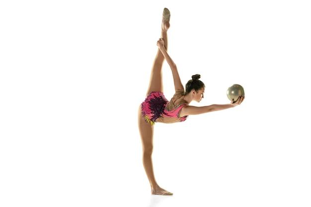 Jovem atleta de ginástica isolada na parede branca do estúdio