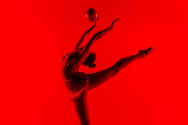 Jovem atleta de ginástica isolada na parede vermelha do estúdio
