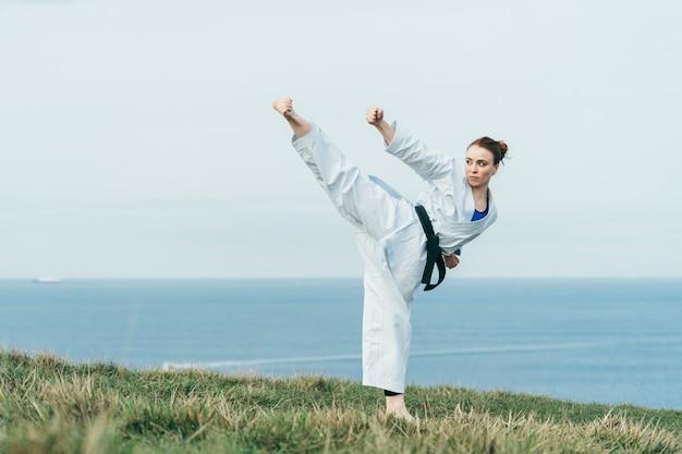 Jovem atleta de karatê ruiva feminina, acertando um chute alto