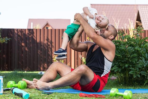 Jovem atleta de pai com seu filho pequeno e alegre entra para a prática de esportes, alongando-se no tatame em um dia quente no jardim perto de casa