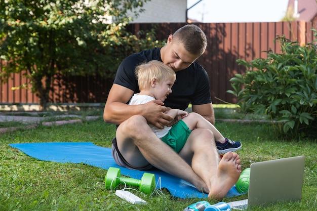 Jovem atleta de pai com seu filho pequeno e alegre pratica esportes no tatame em um dia quente no jardim perto de casa