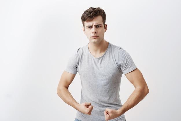 Jovem atleta do sexo masculino caucasiano com corpo musculoso, demonstrando o quão forte ele é, se orgulha de si mesmo. cara positiva franze a testa, mostra músculos e força, tem expressão confiante, pronta para lutar.