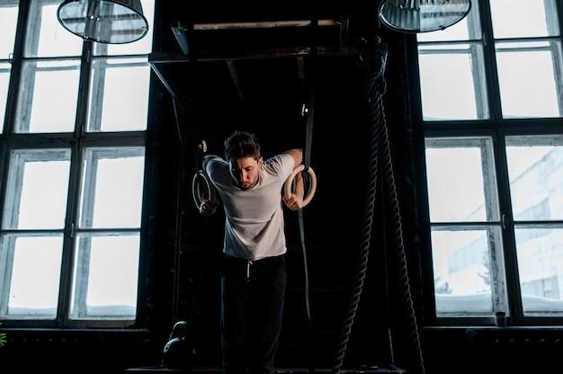 Jovem atleta do sexo masculino com argolas de ginástica na academia em foco na foto de alta qualidade dos anéis