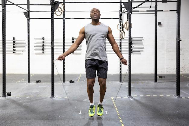 Jovem atleta do sexo masculino pulando corda no ginásio. conceito de cuidados com o corpo.