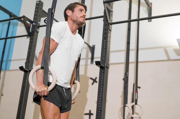 Jovem atleta do sexo masculino se exercitando com argolas de ginástica na academia