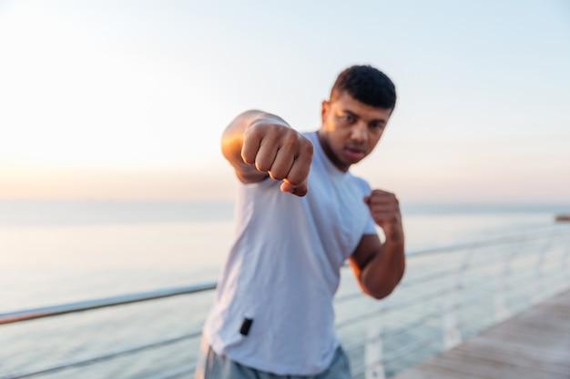 Jovem atleta em pé fazendo treinamento de boxe no cais