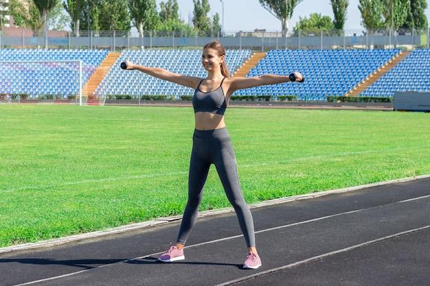 Jovem atleta feminina com halteres, alongamento e aquecimento na pista de corrida no conceito de esporte e fitness stadium