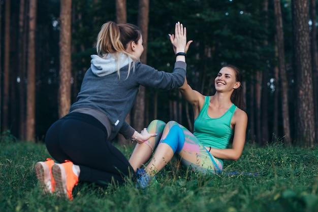 Jovem atleta feminina malhando com um treinador fazendo flexões dando mais cinco