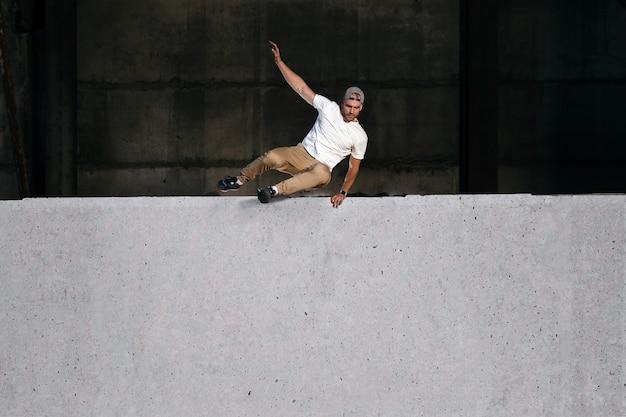 Jovem atleta forte de parkour e corrida livre pulando o muro em ambiente urbano