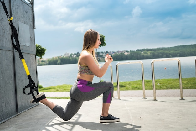 Jovem atleta magro treinando usando trx na natureza. estilo de vida saudável. faça seu corpo máquina