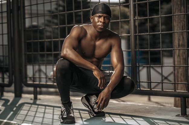 Jovem atleta masculino posando de treino de verão estilo saudável