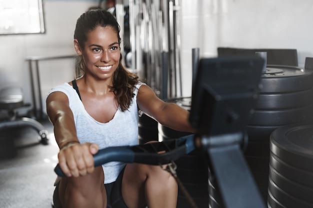 Jovem atleta motivada, sorrindo na academia, usando equipamento de leg press
