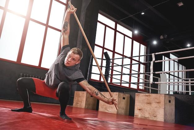 Jovem atleta musculoso focado em roupas esportivas coloridas, aquecendo seus músculos antes de treinar na academia de boxe preto