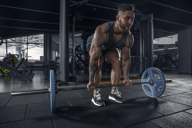 Jovem atleta musculoso praticando flexões na academia com barra