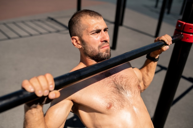 Jovem atleta musculoso sem camisa praticando flexões enquanto se segura no bar de esportes durante exercícios ao ar livre nas instalações