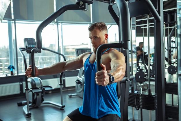 Jovem atleta musculoso treinando na academia, fazendo exercícios de força, praticando