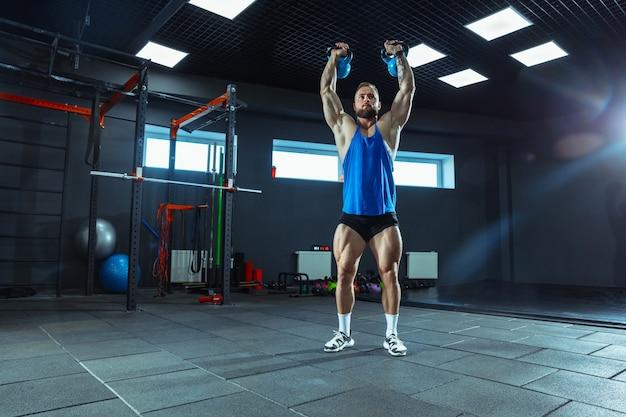 Jovem atleta musculoso treinando na academia, fazendo exercícios de força
